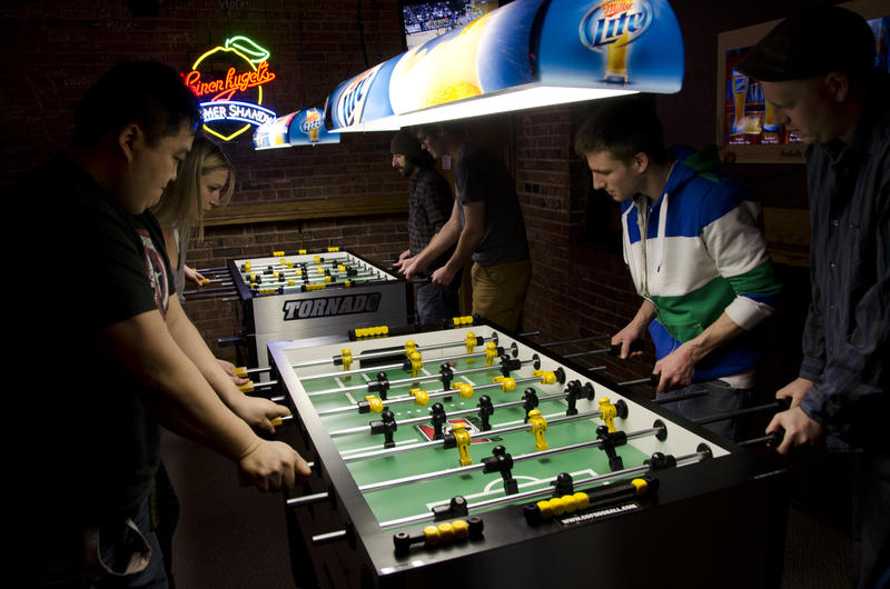 Football fans playing foosball